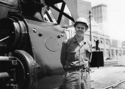 John C. Clarke at the Roundhouse, early 1970s. Posing in front of a steam locomotive